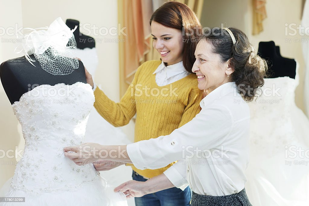 mother  with daughter chooses bridal gown stock photo
