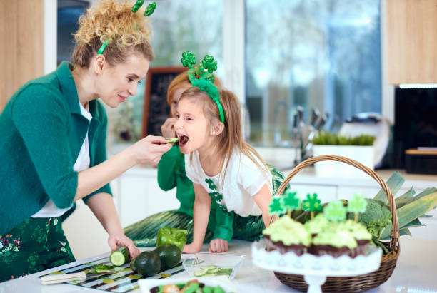 mother with daughter cooking at kitchen - happy st. patricks day stock photos and pictures