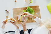 Mother with daughter eating sandwiches at home in the kitchen, top view