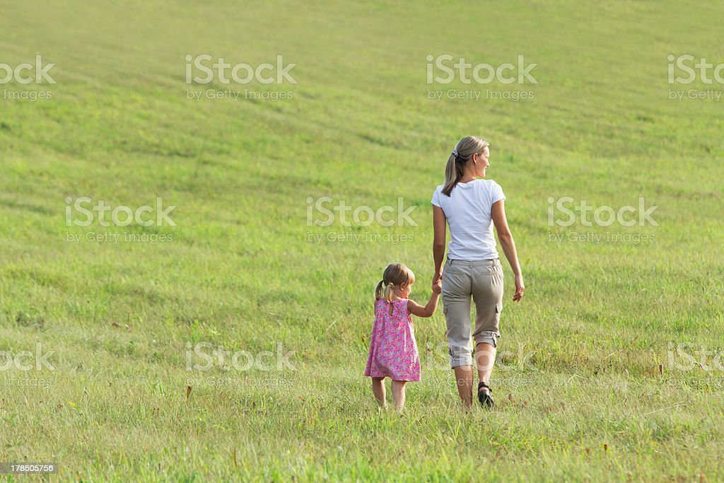 Mother with daughter go on grass in clean floor royalty-free stock photo
