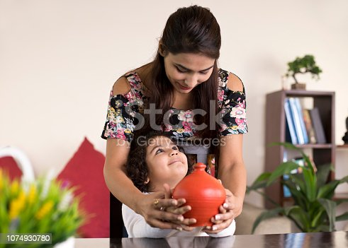 Indian mother with daughter holding piggy bank at home