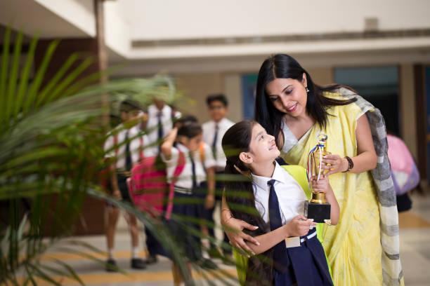 Mutter mit Tochter hält Trophäe in der Schule – Foto