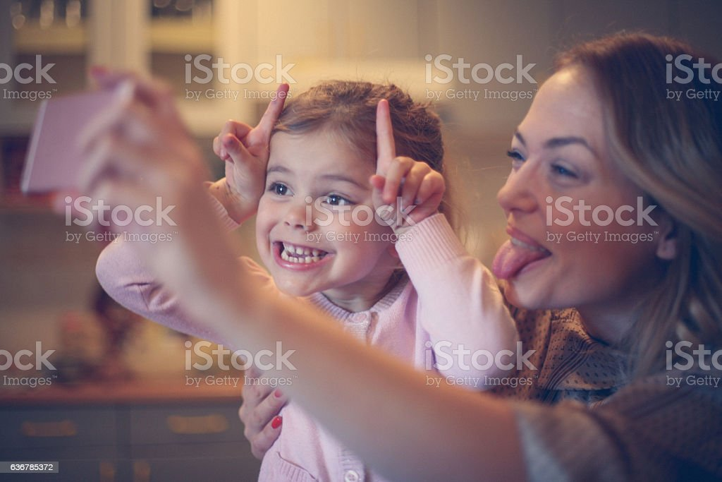 Mother with daughter making funny face. stock photo