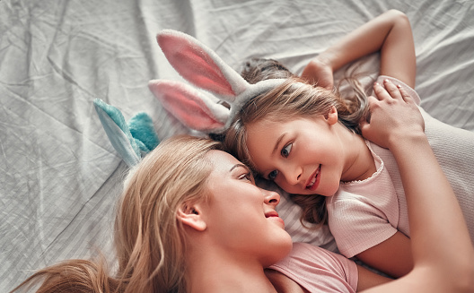 Attractive young woman with her cute little daughter lying on bed together wearing bunny ears. Celebrating Easter.