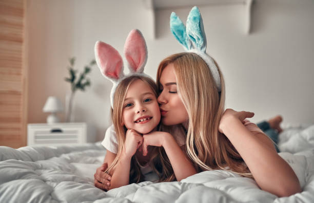 Mother with daughter on bed stock photo