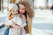 A young and stylish mom plays with her little beautiful daughter in a snowy snowy park