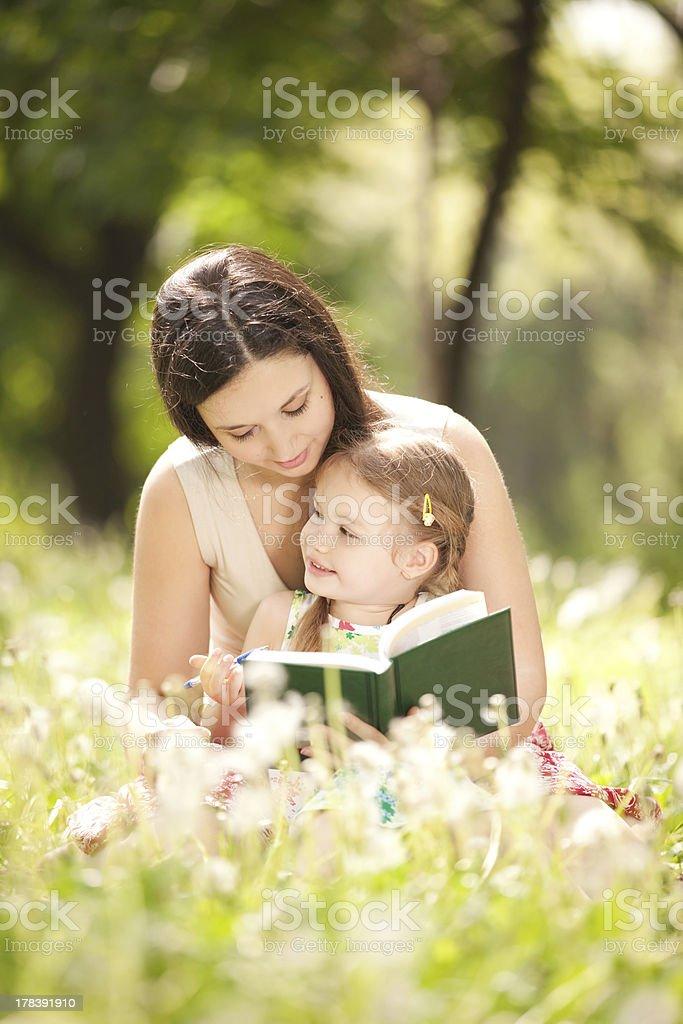 Mutter mit Tochter lesen Sie ein Buch im park – Foto