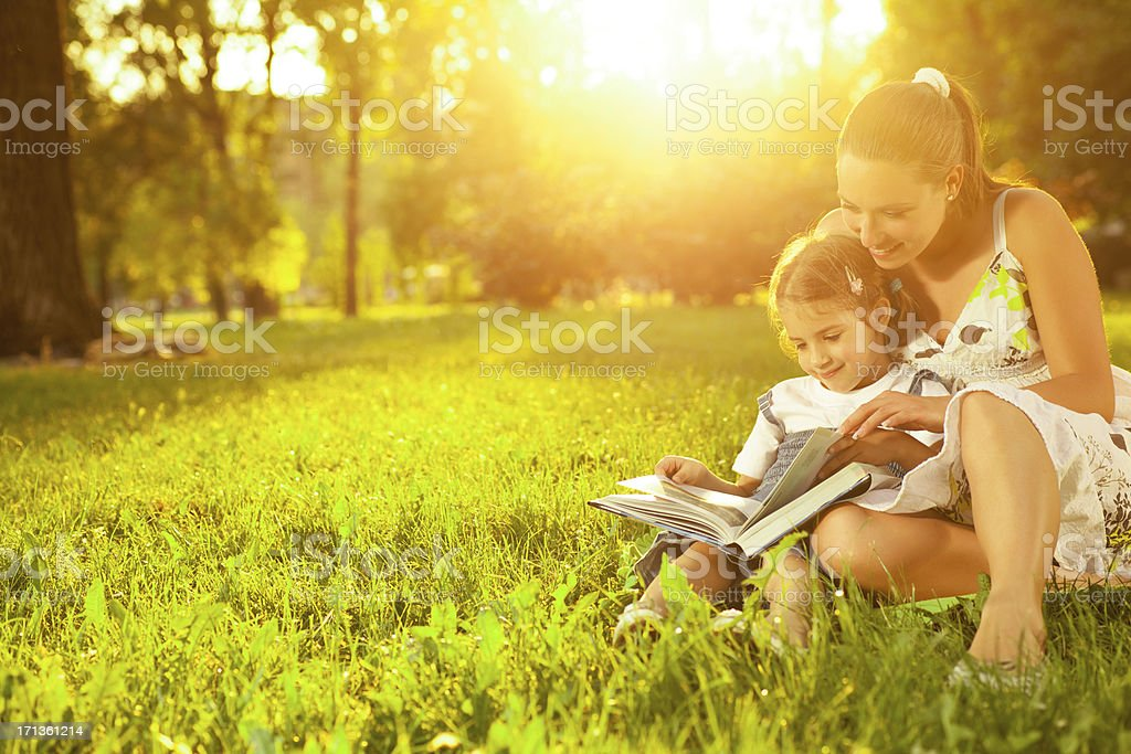 Mother with daughter  reading book outdoor royalty-free stock photo