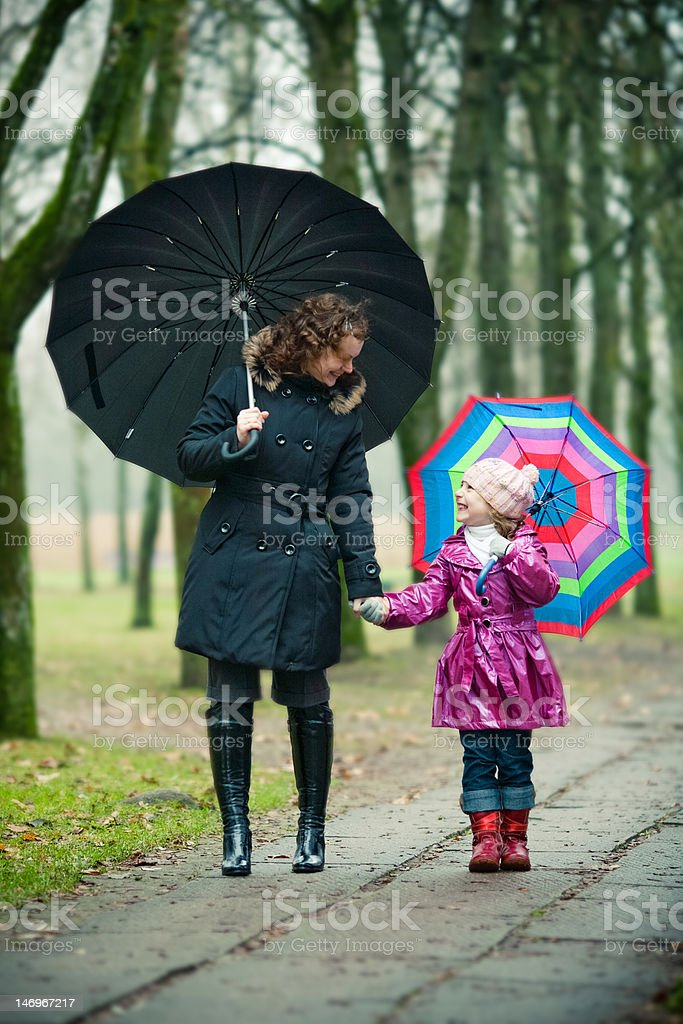 mother with daughter under umbrellas royalty-free stock photo