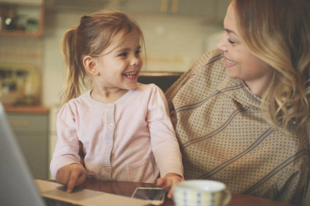 mother with daughter using laptop. - happy mothers day type stock photos and pictures