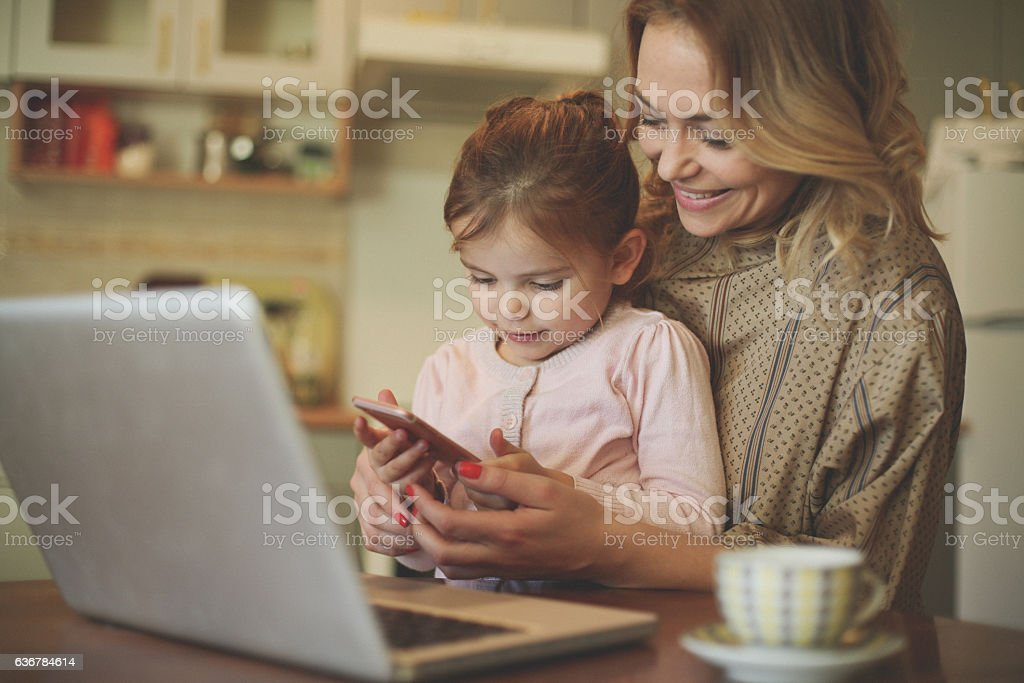 Mother with daughter using mobile phone. stock photo