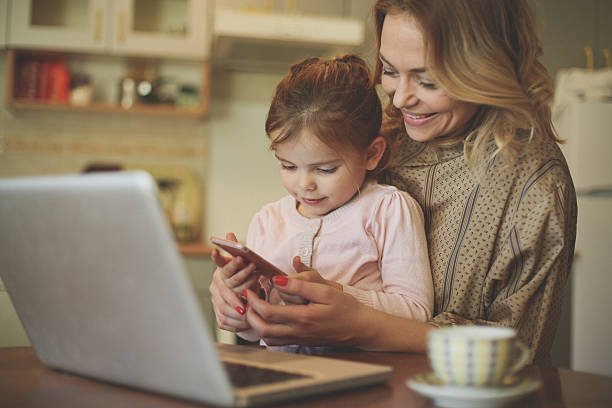 mother with daughter using mobile phone. - femmes actives photos et images de collection