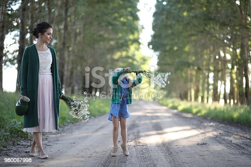 Beautiful young mother with daughter walking on a rural road