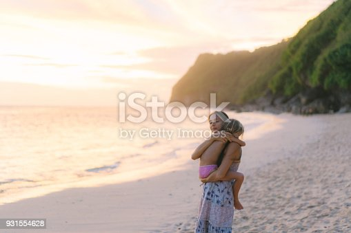 929671306 istock photo Mother  with daughter  walking on the beach in Bali 931554628