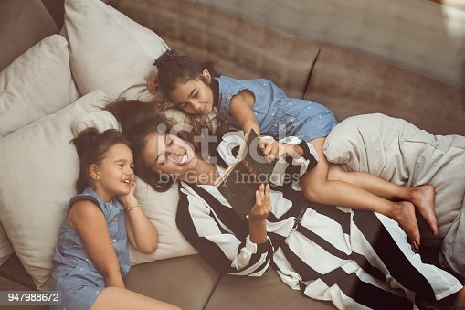 Relaxed woman with two daughters on the sofa reading a book