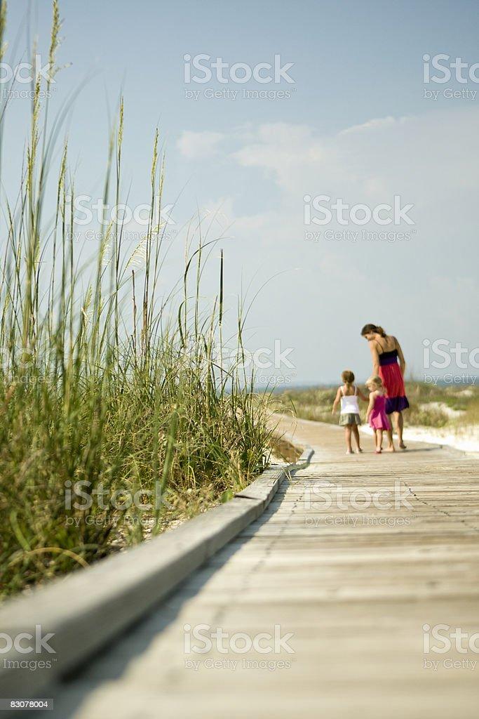 Mother with daughters strolling on beach boardwalk royaltyfri bildbanksbilder