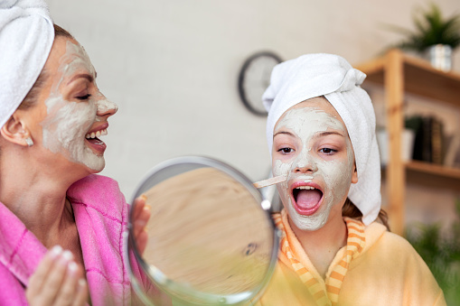 Mother with dauhtrer with facial mask of natural ingredients feeling happy at home