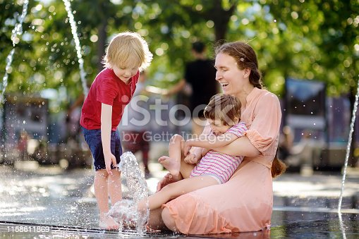 Mother with disabled girl and boy having fun on fountain at sunny summer park. Child cerebral palsy. Family with disabled kid. Inclusion.