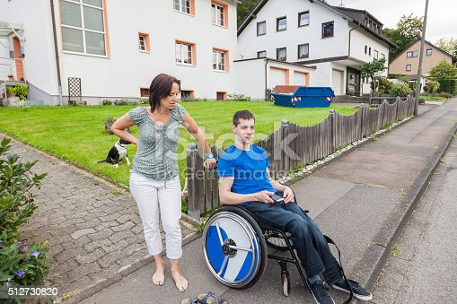 466456685 istock photo Mother with handicapped son waiting for the school bus 512730820