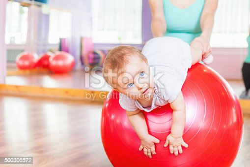 istock Mother with happy baby doing exercises with gymnastic ball 500305572