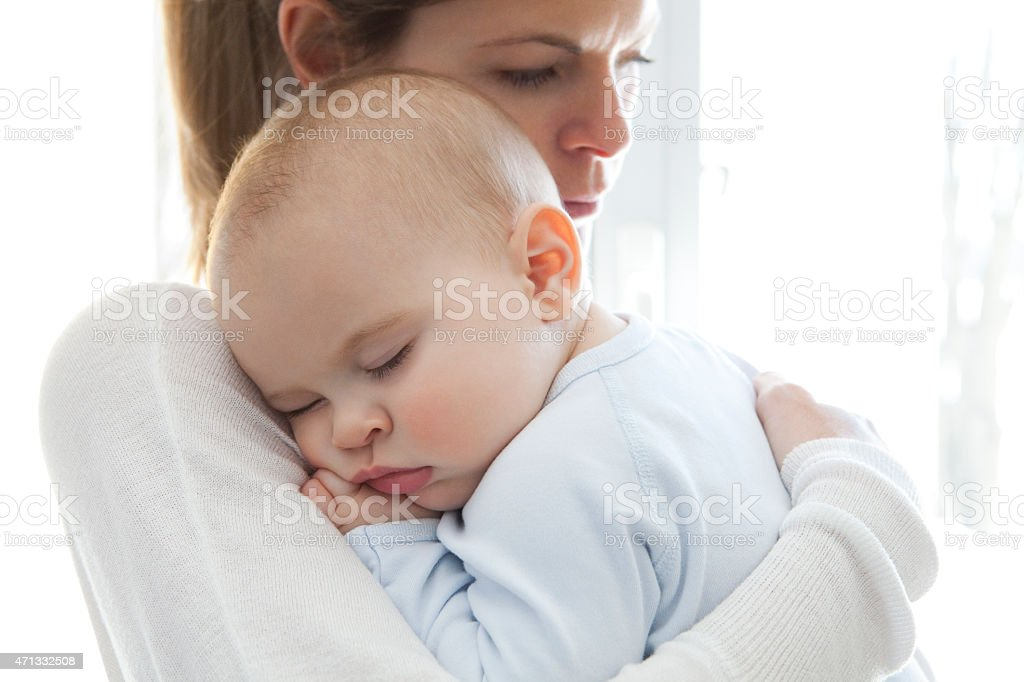 Mother With Her Baby Boy Sleeping In Her Arms royalty-free stock photo
