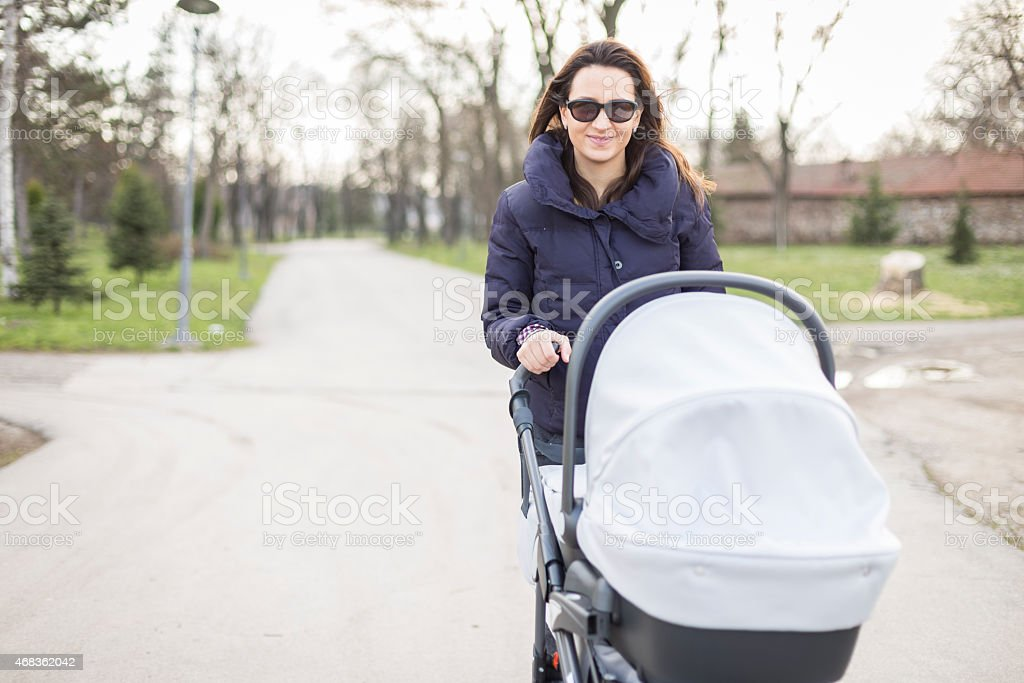 Mother with her baby in a stroller spending time together royalty-free stock photo