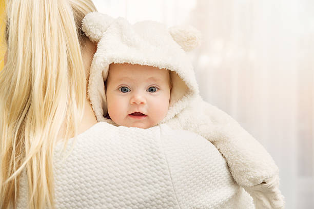 mother with her baby in fluffy bear costume over shoulder stock photo