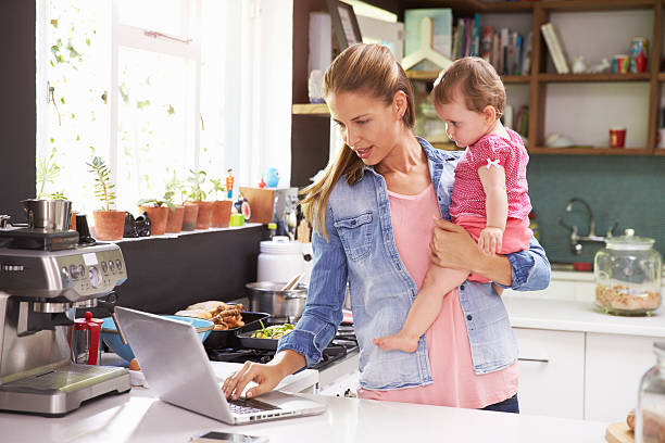 mother with her baby using a laptop in the kitchen - day in the life series stock pictures, royalty-free photos & images
