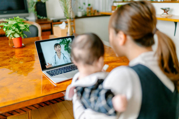 mother with her baby video calling doctor from home - telemedicine stock pictures, royalty-free photos & images