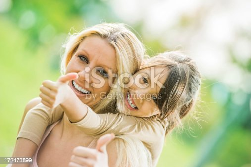 Cheerful mother is piggybacking her cute daughter. They are showing thumbs up.