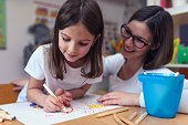 Mother with her child having creative and fun time drawing