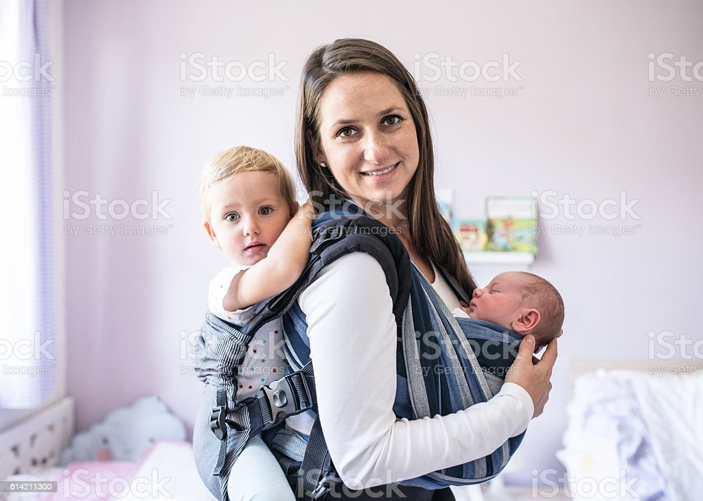 Mother with her children in sling and baby carrier stock photo