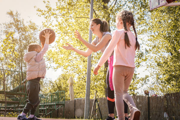 Mother with her children playing basketball. stock photo