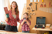 Mother with her cute little daughter in wood shop working on a project. Making something out of wood. They are holding work tools and posing at camera. Wearing similar plaid shirts. Caucasian, day time. Lean in.