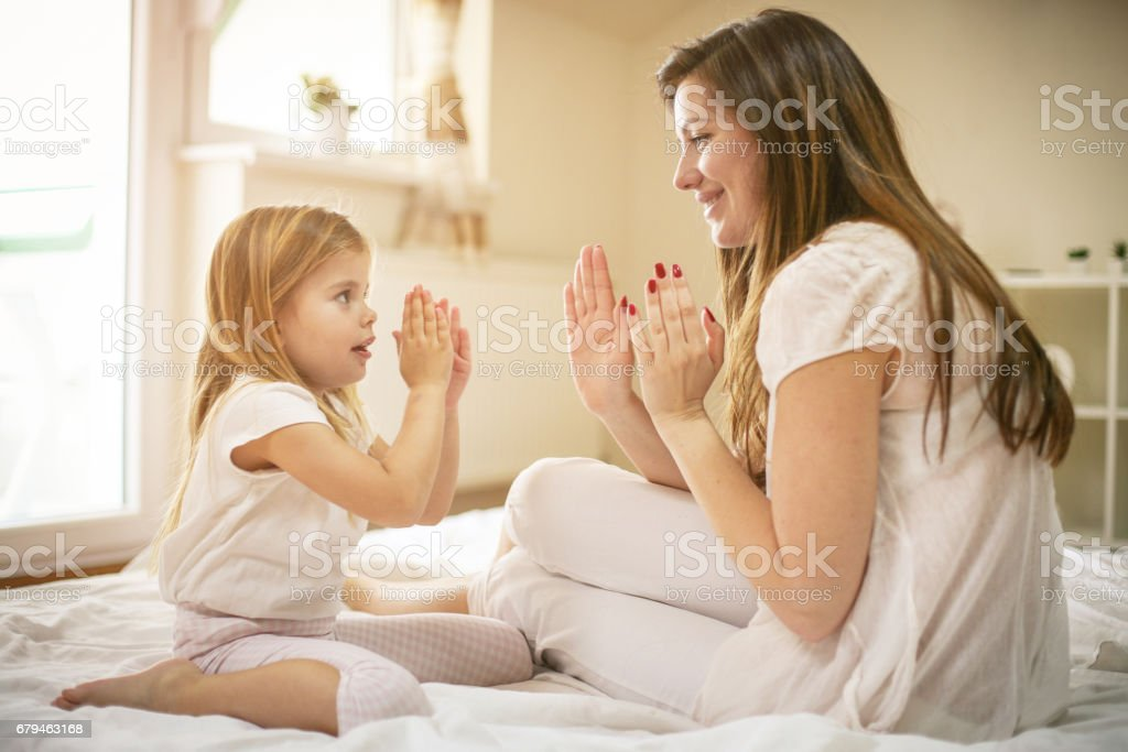 Mother with her cute little daughter sitting on bed. royalty-free stock photo