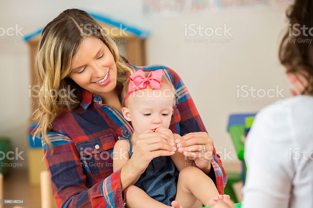 Mother with her cute toddler daughter practice sign language stock photo