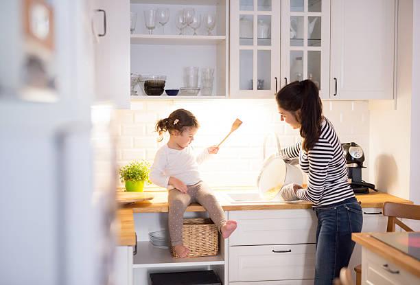 mother with her daughter in the kitchen cooking together - kinderküche zubehör stock-fotos und bilder