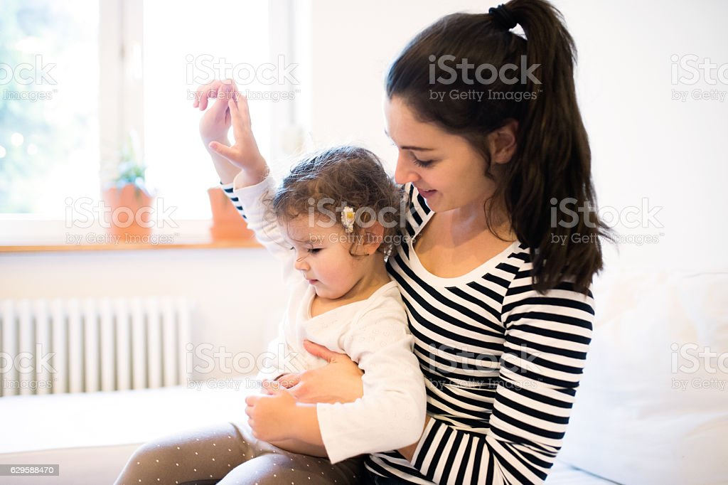 Mother with her daughter in the morning on a couch stock photo