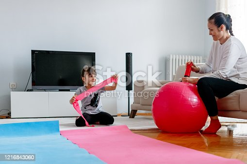 916126642 istock photo mother with her daughter is preparing to do sports at home 1216843060