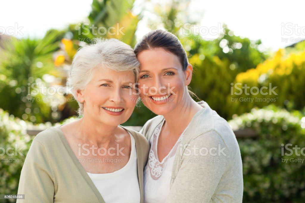 Mutter mit ihrer Tochter schaut in die Kamera im Garten – Foto