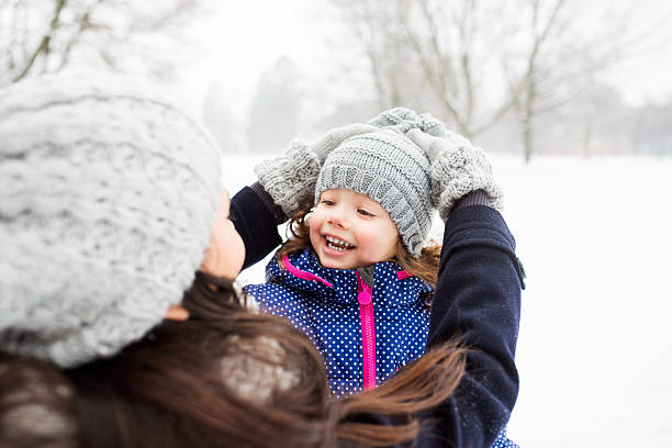 mother with her daughter playing outside in winter nature - winterjacke lang damen stock-fotos und bilder