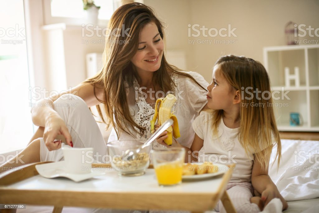 Mother with her little daughter having breakfast in the bed. stock photo