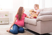 istock Mother with her little daughter sitting on sofa 922448698