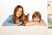 happiness family with notepad and york terrier on blossoming tree background
