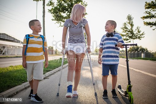 Mother with her sons walking using crutches