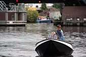 Akkrum, the Netherlands, - August 11, 2017. Mother with here son on a small boat coming in to the harbor of Akkrum.