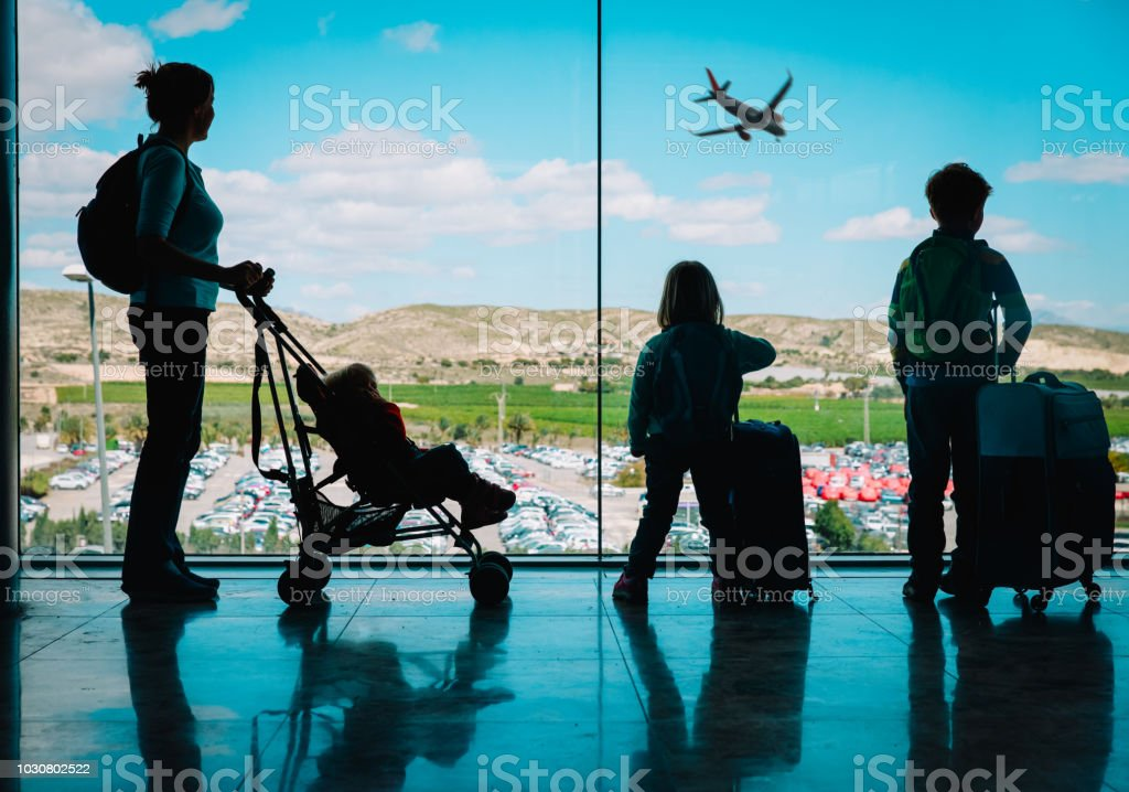 mother with kids and luggage looking at planes in airport - Royalty-free Adult Stock Photo