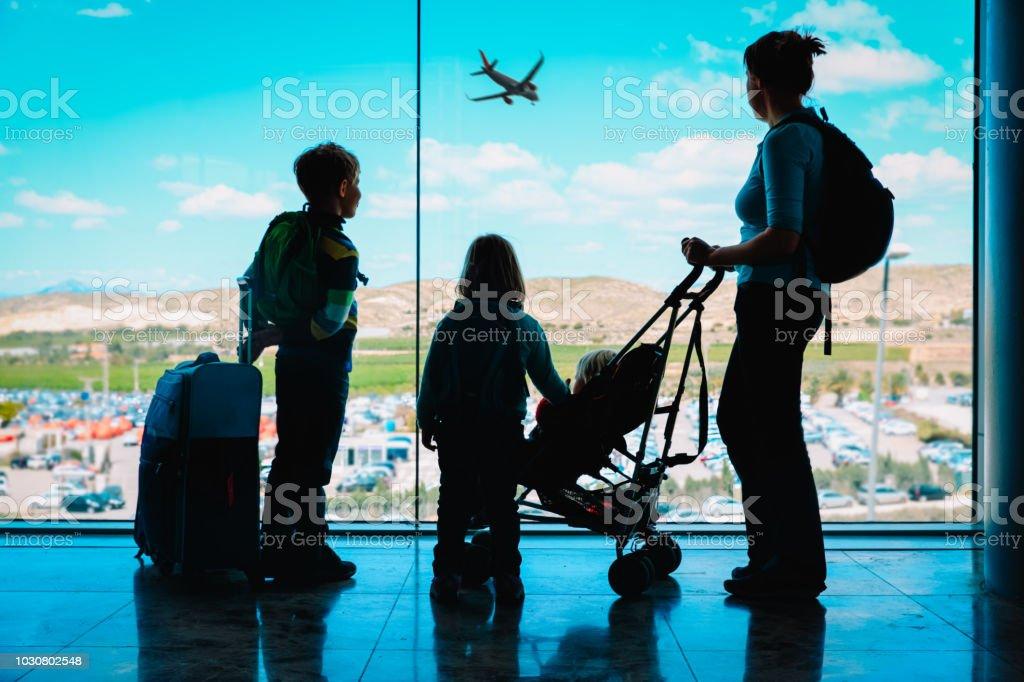 子供と荷物を空港で飛行機を見て母 ストックフォト