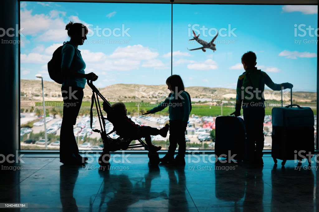 mother with kids and luggage looking at planes in airport royalty-free stock photo