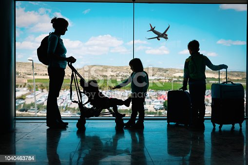 mother with kids and luggage looking at planes in airport, family travel